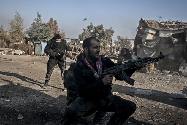 Free Syrian Army fighters fire their weapons during heavy clashes with government forces in Aleppo, Syria, Sunday, Jan. 20, 2013. The revolt against President Bashar Assad began in March 2011with peac