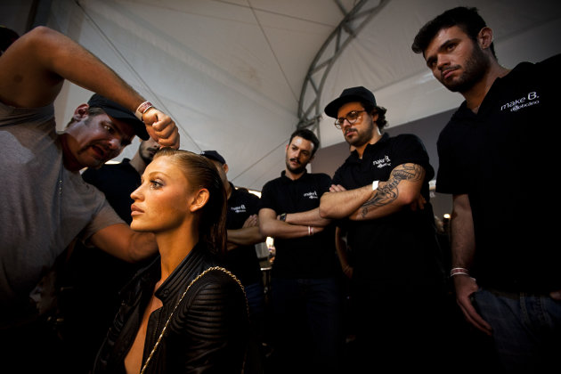 A hair stylist arranges a model's hair as other stylists watch during the preparation backstage for the catwalk presentation of summer collection designs by Lenny at Fashion Rio in Rio de Janeiro, Bra