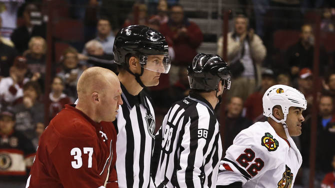 Phoenix Coyotes' Raffi Torres (37) and Jamal Mayers (22) are taken to the penalty box by linesmen John Grandt (98) and Shane Heyer after fighting during the first period in an NHL hockey game Thursday, Feb. 7, 2013, in Glendale, Ariz.(AP Photo/Ross D. Franklin)
