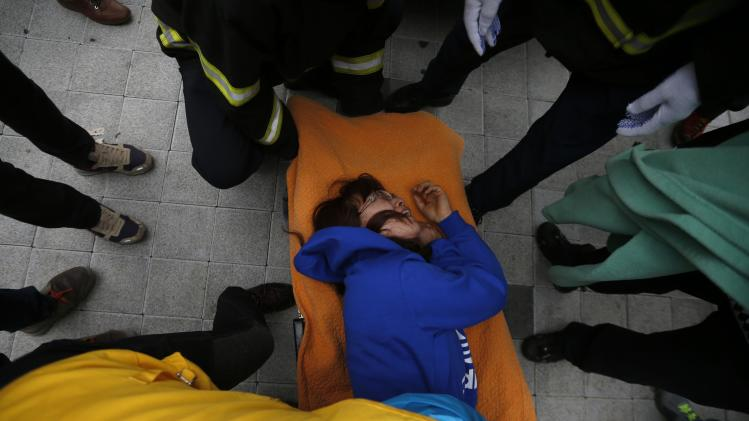 "A family member of a missing passenger who was on South Korean ferry ""Sewol"" which sank at the sea off Jindo is wheeled into an ambulance after collapsing as she waits for news of their family from a rescue team at a gym in Jindo"