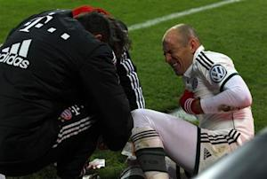 Bayern Munich's Robben reacts as medical assistants attend to his leg during third round German soccer cup match in Augsburg