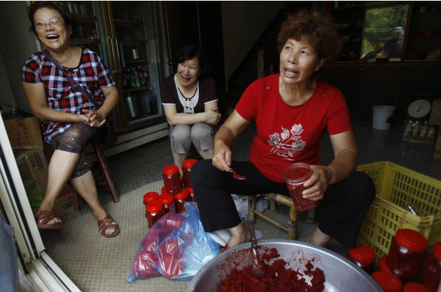 In this Aug. 21, 2012 photo,  Lin, in red, sits with friends as they fill jars of red sorgum, a local delicacy, and talk about why they voted for the proposed casino to be built on Beigan in the Matsu