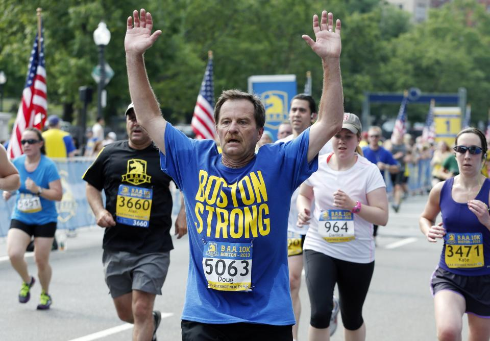 Doug Lyons, center, of Cotuit, Mass., finishes the Boston Athletic Association 10k in Boston, Sunday, June 23, 2013. More than 6,400 runners took part in Boston's first major race since the April marathon bombings that killed three people and injured hundreds of others. (AP Photo/Michael Dwyer)