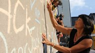 NDP MP Olivia Chow writes on a wall full of tributes to her husband Jack Layton in Toronto before a memorial event dedicated to the former NDP leader.