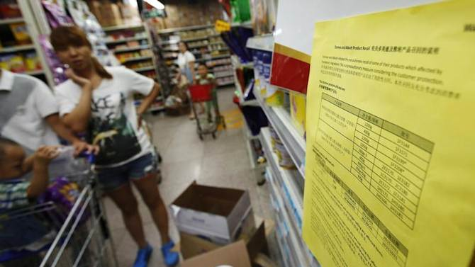 A woman looks at a notice about the product recall of some of Dumex and Abbott's milk powder products at a supermarket in Beijing