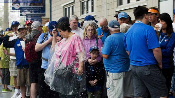 Fans take cover during a rain delay as the Toronto Blue Jays wait to play against the Baltimore Orioles in a spring training baseball game in Dunedin, Fla., Friday, March 6, 2015. (AP Photo/The Canadian Press, Nathan Denette)