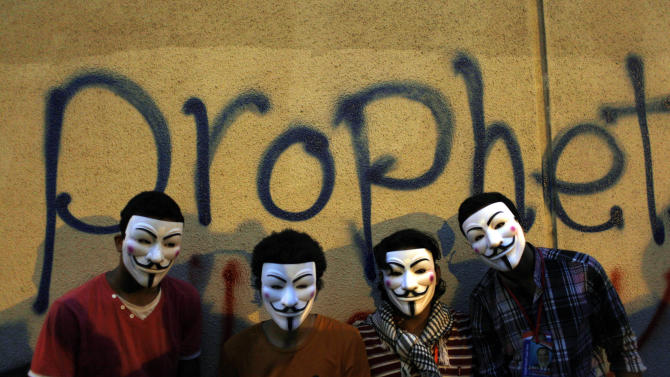 Egyptian protesters wearing Guy Fawkes masks pose for a photo graffiti on a wall of the U.S. embassy during a protest in Cairo, Egypt, Tuesday, Sept. 11, 2012. Egyptian protesters, largely ultra conservative Islamists, have climbed the walls of the U.S. embassy in Cairo, went into the courtyard and brought down the flag, replacing it with a black flag with Islamic inscription, in protest of a film deemed offensive of Islam. (AP Photo/Nasser Nasser)