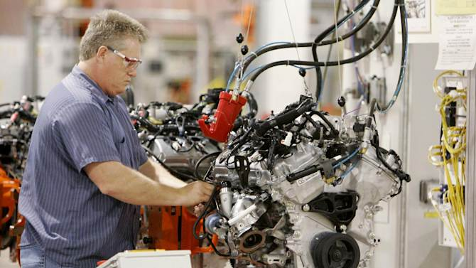 FILE-This Tuesday, May 19, 2009 file photo shows Larry Warner pressure testing lines for the turbocharger on Ford's EcoBoost V-6 at Cleveland Engine Plant No. 1 in Brook Park, Ohio. Ford is moving production of a popular small engine from Spain to Cleveland as sales of four-cylinder motors continue to rise. (AP Photo/Mark Duncan, File)