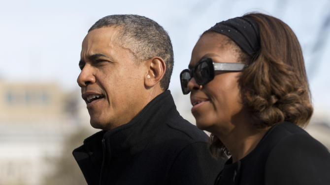 President Barack Obama and first lady Michelle Obama walk across the South Lawn of the White House from Marine One, Sunday, March 9, 2014, in Washington, as they arrive from Florida. (AP Photo/Carolyn Kaster)
