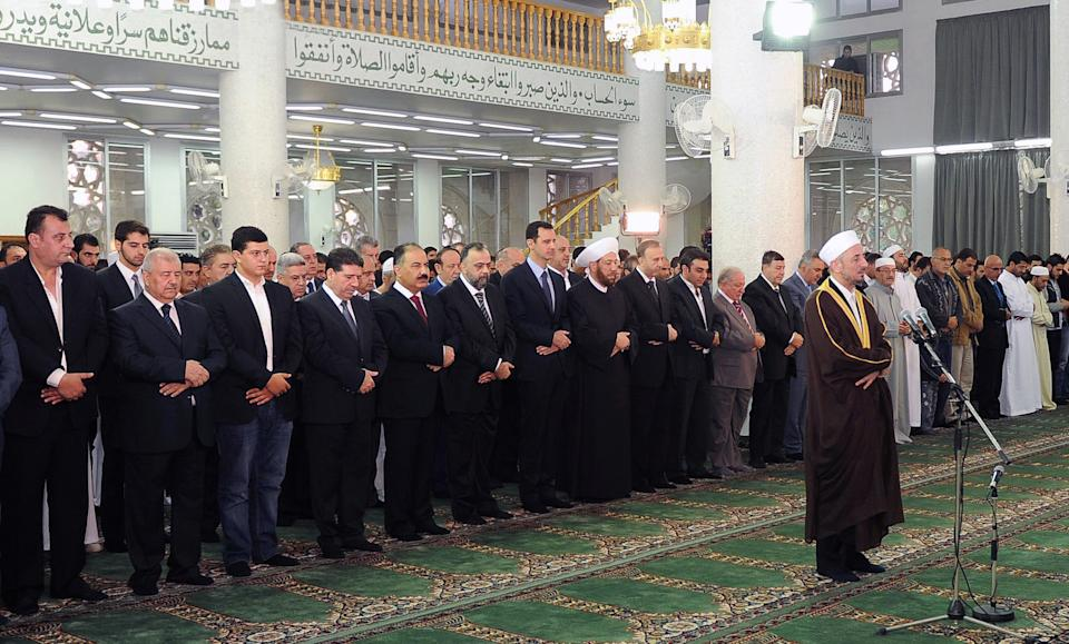 In this photo released by the Syrian official news agency SANA, Syrian President Bashar Assad, center background, prays during the Eid al-Adha prayer at the Sayeda Hassiba mosque, in Damascus, Syria, Tuesday, Oct. 15, 2013. (AP Photo/SANA)