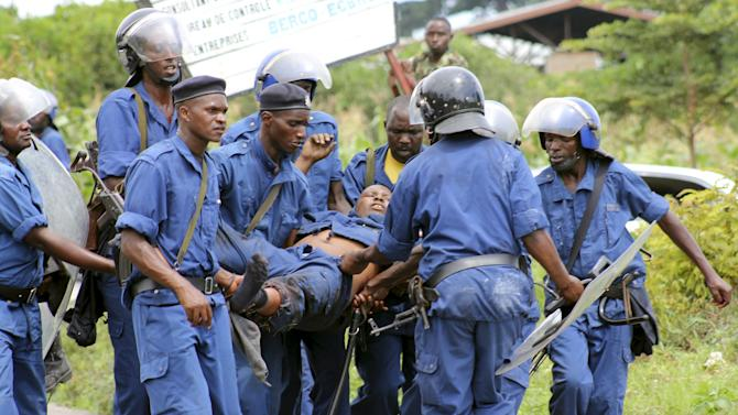 Riot policemen evacuate their colleague after he was injured during clashes with protesters against the ruling CNDD-FDD party's decision to allow Burundian PresidentNkurunziza to run for a third five-year term in office, in Bujumbura