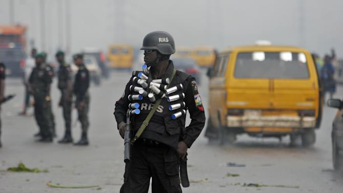 A police officer carrying canisters of tear gas stands guard after a protest on the Third Mainland Bridge in Lagos, Nigeria, Wednesday, May 30, 2012.  Students from the University of Lagos and unemployed youths shut down the major bridge in Lagos on Wednesday while protesting a proposed name change for their university.  On Tuesday, President Goodluck Jonathan said the University of Lagos would be renamed Moshood Abiola University in honor of a political prisoner who died in jail over a decade ago. (AP Photo/Jon Gambrell)