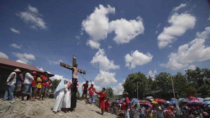 CORRECTS CITY - A Filipino penitent is nailed to the cross during Good Friday rituals on Friday, March 29, 2013 at San Juan, Pampanga province, northern Philippines. Several Filipino devotees had themselves nailed to crosses Friday to remember Jesus Christ's suffering and death, an annual rite rejected by church leaders in this predominantly Roman Catholic country. (AP Photo/Aaron Favila)