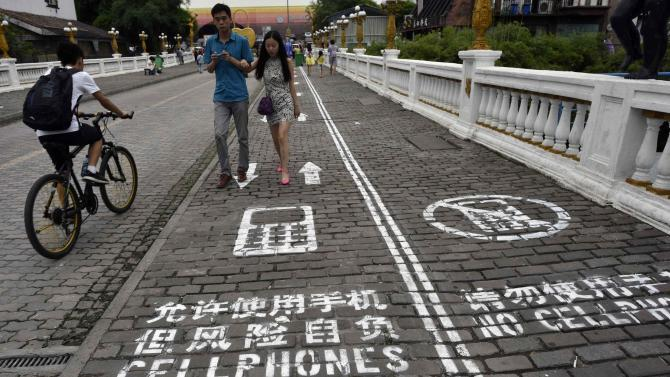 """A man rides his bicycle as people walk on the """"first mobile phone sidewalk in China"""", which was recently installed at a tourism area in Chongqing municipality"""