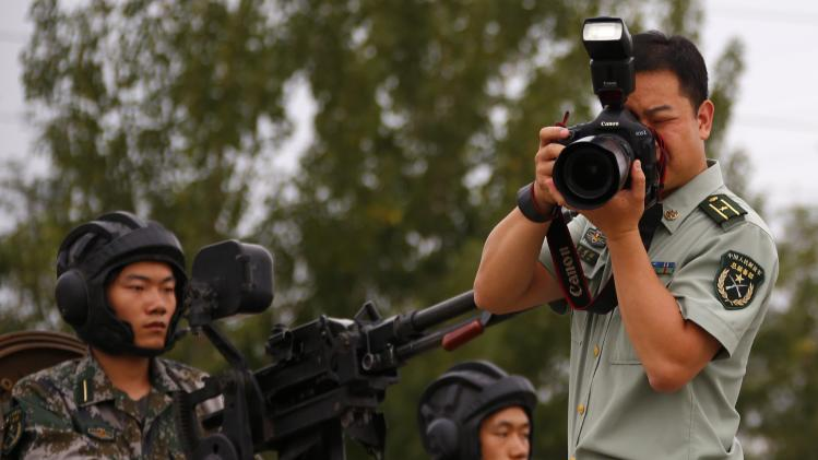 A soldier of the People's Liberation Army (PLA) takes pictures of a drill during an organised media tour at a PLA engineering academy in Beijing