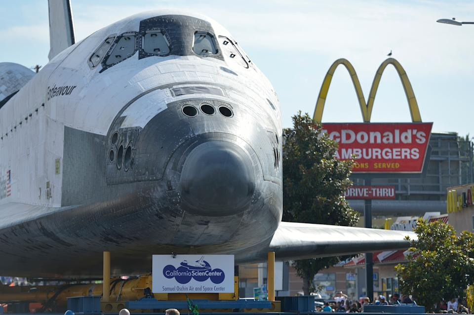 The space shuttle Endeavour travels past a fast food restaurant along on Crenshaw Blvd. enroute to the California Science Center during its final journey in Los Angeles, Calif. on Saturday, Oct. 13, 2012. (AP Photo/Jeff Gritchen, Pool)