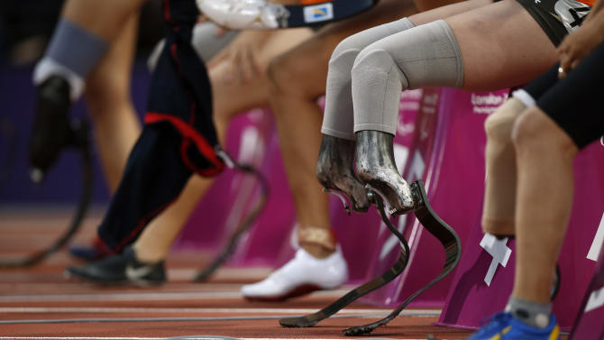 Marlou van Rhijn from the Netherlands, second right, sits as she waits to be called up into the blocks before the start of a women's 100m T44 round 1 race at the 2012 Paralympics in London, Saturday, Sept. 1, 2012.  Van Rhijn ran a new world record in the race of 13.27 seconds.  (AP Photo/Matt Dunham)