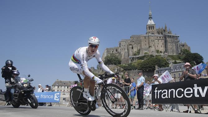 Tony Martin of Germany passes world heritage site Mont-Saint-Michel, rear, a rocky tidal island which holds a monastery, during the eleventh stage of the Tour de France cycling race, an individual time trial over 33 kilometers (20.6 miles) with start in in Avranches and finish in Mont-Saint-Michel, western France, Wednesday July 10 2013. (AP Photo/Laurent Cipriani)