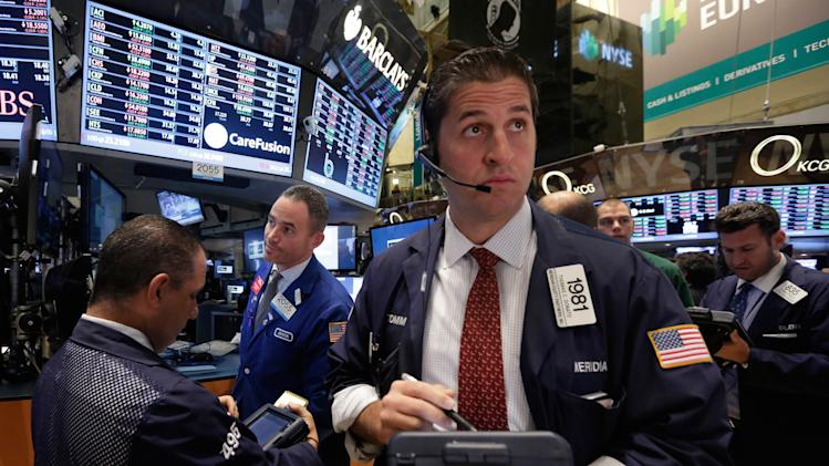 Trader Thomas Donato, center, works on the floor of the New York Stock Exchange, Tuesday, Nov. 19, 2013. Stocks are lower in early trading on Wall Street as traders pick over some disappointing corporate earnings. (AP Photo/Richard Drew)