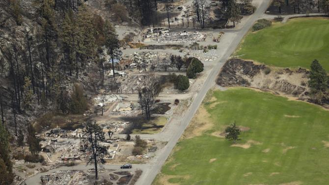 Remains of buildings burned by wildfires lies across the road from the Alta Lake Golf Course near Pateros, Wash., in this Thursday, July 24, 2014, aerial photo. (AP Photo)