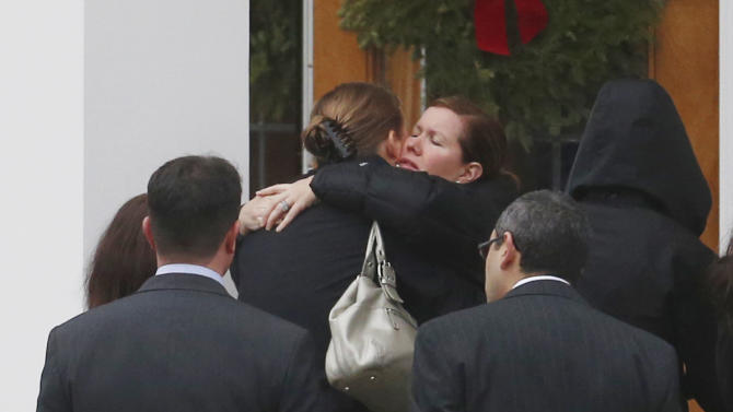 Mourners embrace outside of St. Rose of Lima Roman Catholic Church during funeral services for James Mattioli, Tuesday, Dec. 18, 2012, in Newtown, Conn. Mattioli, 6, was killed when Adam Lanza walked into Sandy Hook Elementary School in Newtown, Conn., Dec. 14,  and opened fire, killing 26 people, including 20 children, before killing himself. (AP Photo/Julio Cortez)