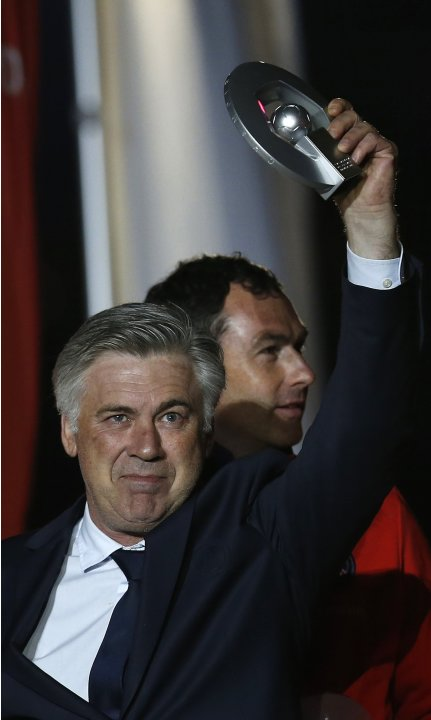 Paris Saint-Germain's coach Ancelotti raises his French Championship trophy after his team's French Ligue 1 soccer match against Brest at the Parc des Princes stadium in Paris