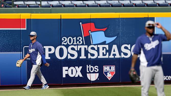 Los Angeles Dodgers manager Don Mattingly walks by a postseason sign during baseball practice Wednesday, Oct. 2, 2013, in Atlanta. The Dodgers are scheduled to face the Atlanta Braves in Game 1 of the NL division series Thursday. (AP Photo/Atlanta Journal Constitution, Jason Getz) MARIETTA OUT GWINNETT OUT LOCAL TV OUT (WXIA, WGCL, FOX 5)