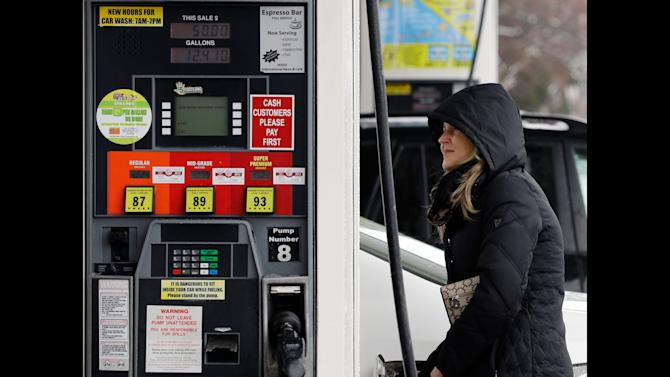 In this Wednesday, Feb. 27, 2013 photo, a woman fills up a gas tank at a gas station in Chicago. A measure of wholesale prices fell by the largest amount in 10 months in March, reflecting a big drop gasoline prices. The Labor Department, on Friday, April 12, 2013, says its producer price index fell 0.6 percent in March compared with February. In February, wholesale prices had jumped 0.7 percent. (AP Photo/Nam Y. Huh)