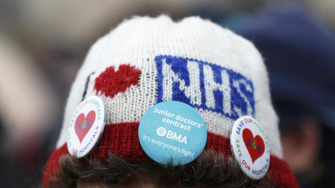 """A demonstrator wears a hat that reads """"I Love NHS"""" during a protest in central London"""