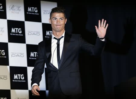 Real Madrid's Ronaldo waves upon arriving for a promotional event in Tokyo