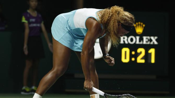 Serena Williams of the U.S. smashes her second racquet during her WTA Finals singles semi-finals tennis match against Caroline Wozniacki of Denmark, at the Singapore Indoor Stadium