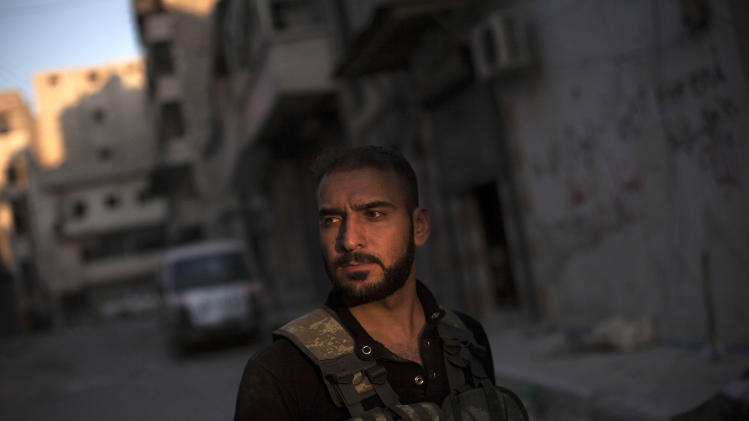 In this Wednesday, Sept. 19, 2012 photo, a Free Syrian Army sniper stands at the front line in the Amariya district in Aleppo, Syria. (AP Photo/Manu Brabo)