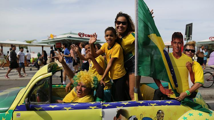 Soccer fans donning Brazil's national team colors wave as they ride past with a life-size cutout of soccer star Neymar, on the Copacabana beachfront in Rio de Janeiro, Brazil, Monday, June 23, 2014. (AP Photo/Leo Correa)