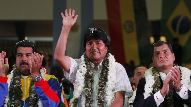 Venezuela's President Nicolas Maduro, left, Ecuador's President Rafael Correa, right, and Bolivia's President Evo Morales acknowledge supporters during a welcome ceremony for presidents attending an extraordinary meeting in Cochabamba, Bolivia, Thursday , July 4, 2013. Leaders of Uruguay, Ecuador, Surinam, Argentina and Venezuela are meeting in Bolivia Thursday in support of Morales, who said said Thursday that the rerouting of his plane in Europe, over suspicions that National Security Agency leaker Edward Snowden was on board was a plot by the U.S. to intimidate him and other Latin American leaders. (AP Photo/Juan Karita)