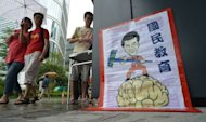 Pedestrians walks past an illustration (R) depicting Hong Kong's chief executive Leung Chun-ying cleaning a brain, during an anti Chinese patriotism classes protest outside of the government headquarters in Hong Kong
