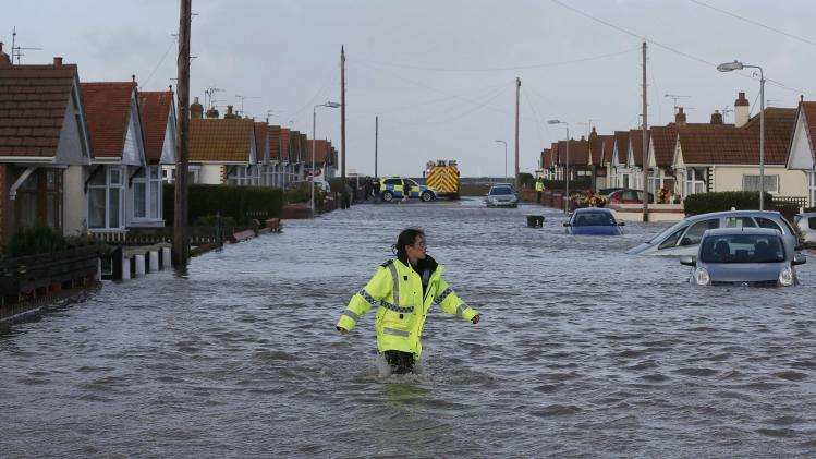 An emergency rescue service worker walks through flood water in a residential street in Rhyl