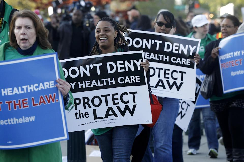 Supporters of the health care reform law signed by President Obama gather in front of the Supreme Court in Washington, Monday, March 26, 2012, as the court begins three days of arguments on health care. (AP Photo/Charles Dharapak)