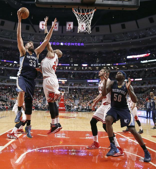 Memphis Grizzlies center Marc Gasol (33) shoots over Chicago Bulls' Taj Gibson (22) as Bulls' Joakim Noah (13) and Grizzlies' Zach Randolph (50) watch during the second half of an NBA bask