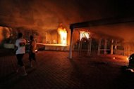 The US consulate buildings burn in Benghazi late on September 11. The White House has struggled to combat a growing storm over the attack on the US consulate in Benghazi, whipped up by Mitt Romney at a fateful moment for President Barack Obama's re-election bid