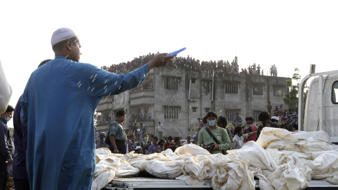 A Bangladeshi Muslim man sprays holy water before burying the bodies of some of the victims of Saturday's fire in a garment factory in Dhaka, Bangladesh, Tuesday, Nov. 27, 2012. Bangladesh held a day of mourning Tuesday for the 112 people killed in a weekend fire at a garment factory, and labor groups planned more protests to demand better worker safety in an industry notorious for operating in firetraps. (AP Photo/Ashraful Alam Tito)