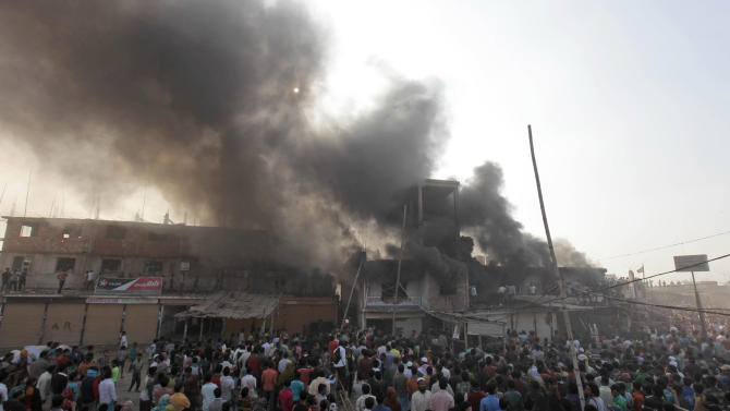 Smoke rises from a two-storied garment factory after a fire swept through it in Dhaka, Bangladesh, Saturday, Jan.26, 2013. The fire swept killed at least six female workers and injured another five, police and fire officials said. The latest fire occurred more than two months after a deadly fire killed 112 workers in another factory near the capital city, raising questions about the safety measures in Bangladesh garment industry. (AP Photo/A.M. Ahad)