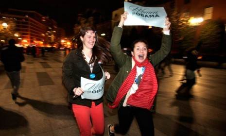 "Revelers holding signs that say ""Women for Obama"" run through the streets after the election is called for the president."