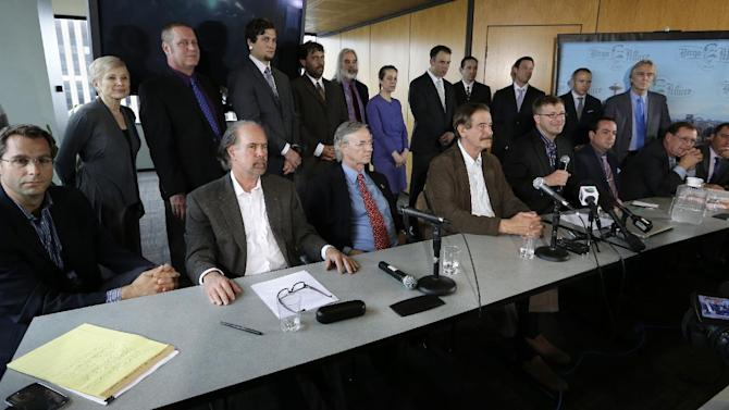 In this photo taken May 30, 2013, Jamen Shively, CEO of Diego Pellicer, seated fourth from right and holding a microphone, speaks during a news conference in Seattle. With visionary zeal, Shively described plans to quickly raise $10 million and to eventually build his company, Diego Pellicer, into an international pot powerhouse and eventually move into the recreational market. But his arrangement with the Seattle medical marijuana company, Northwest Patient Resource Center, was troubling enough to one of its owners, Thomas Jun, that he is walking away from the deal _ and the company he helped found _ because he fears it puts everyone involved at risk of federal prosecution. (AP Photo/Elaine Thompson, File)
