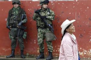 Soldiers stand guard as a woman walks past during a congressional election in Toribio in Cauca province