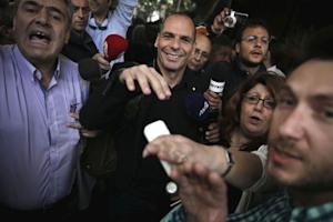 Greek Finance Minister Yanis Varoufakis arrives at his ministry while tax officers demonstrate, outside the building in Athens