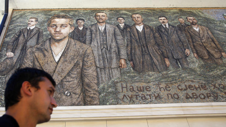 """A man walks past a mosaic depicting Gavrilo Princip, the Bosnian-Serb nationalist who assassinated Archduke Franz Ferdinand in 1914, and other members of """"Mlada Bosna"""" movement in the Bosnian town of Visegrad,140 kilometers east of Sarajevo, Saturday, June 28, 2014. Marking the centennial of the beginning of World War I in their own way, Bosnian Serbs in Visegrad on Saturday unveiled a mosaic of the man who ignited the war by assassinating the Austro-Hungarian crown prince on June 28, 1914. (AP Photo/Darko Vojinovic)"""