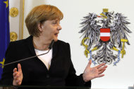 <p>               German Chancellor Angela Merkel speaks at a press conference at the federal chancellery in Vienna, Austria, Friday, Sept. 7, 2012. In background Austria's coat of arms.  (AP Photo/Ronald Zak)