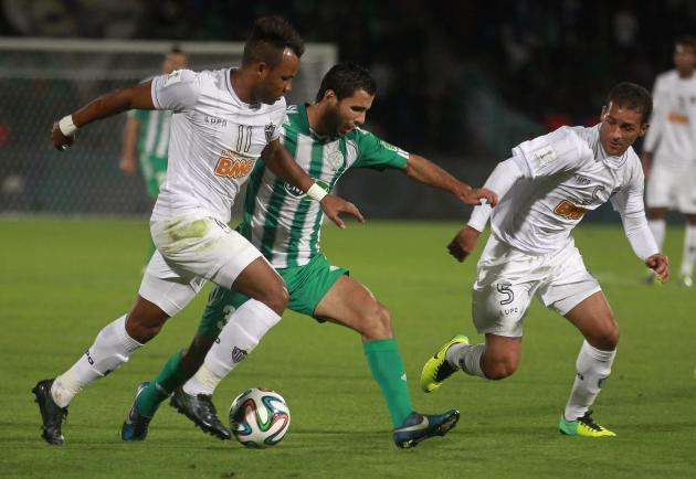 Raja Casablanca's El Hachimi fights for the ball with Atletico Mineiro's Pierre and Fernandinho during their FIFA Club World Cup semi-final soccer match at Marrakech stadium
