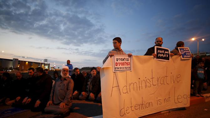 Demonstrators pray as some hold signs calling for the release of Palestinian journalist Mohammed al-Qeq, outside Haemek hospital where he is receiving medical treatment in the northern Israeli city of Afula