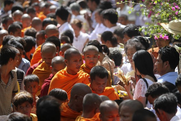 People offer food and money to Buddhist monks during the Vesak Day ceremony at the Udong mountain in Kandal